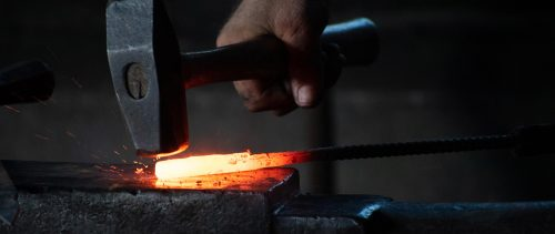 forging hot steel with hammer on anvil